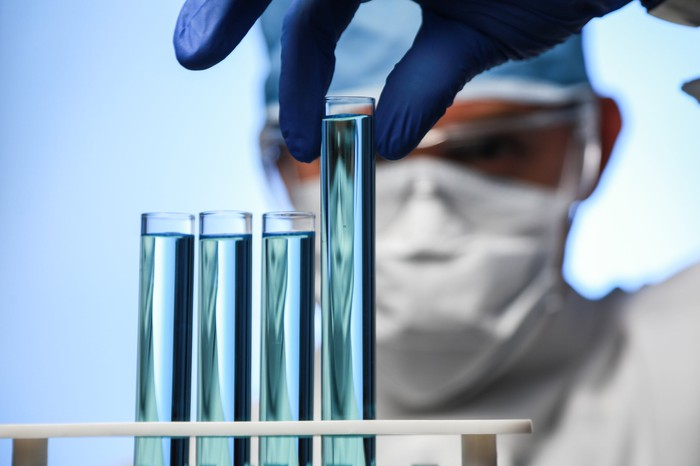 Scientist picking up a test tube with bluish liquid from a rack with three other test tubes.