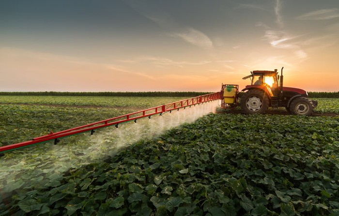 A tractor applying topicals to crops.