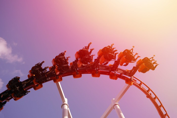 Riders on a roller coaster on a sunny day.