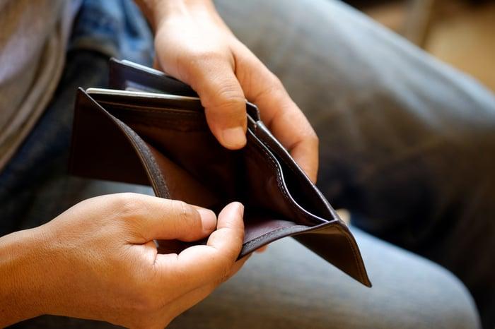 Man holding empty wallet open