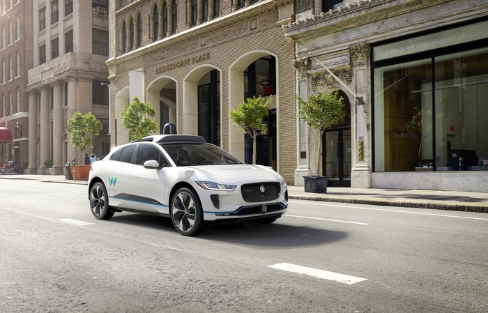 Jaguar I-PACE with a Waymo logo driving in the city