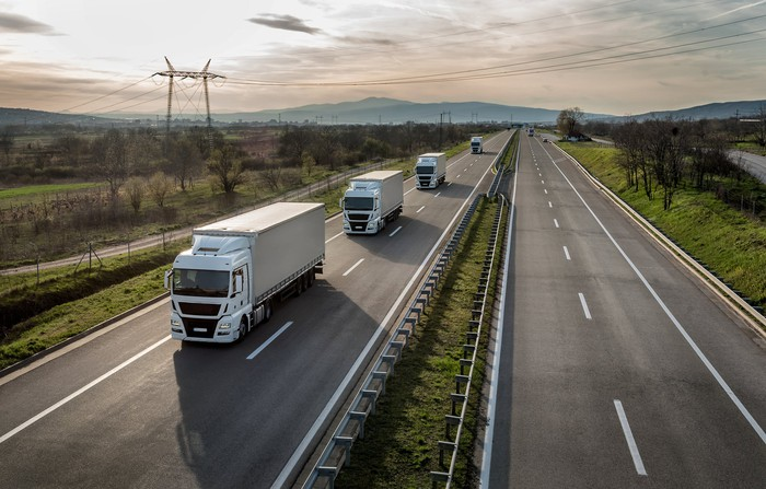 Four trucks going on way on an empty road