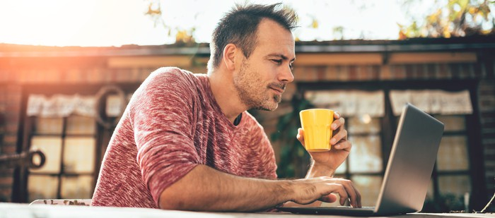 Man sitting in front of his laptop outdoors holding a drink in a yellow cup.