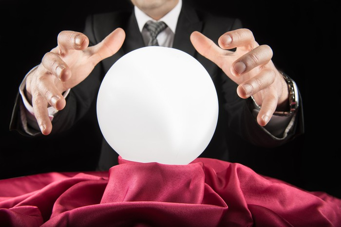 A fortune teller waving his hands above a crystal ball on a table in front of him.