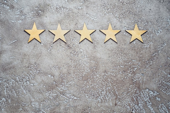 Five gold stars in a row on a concrete floor.