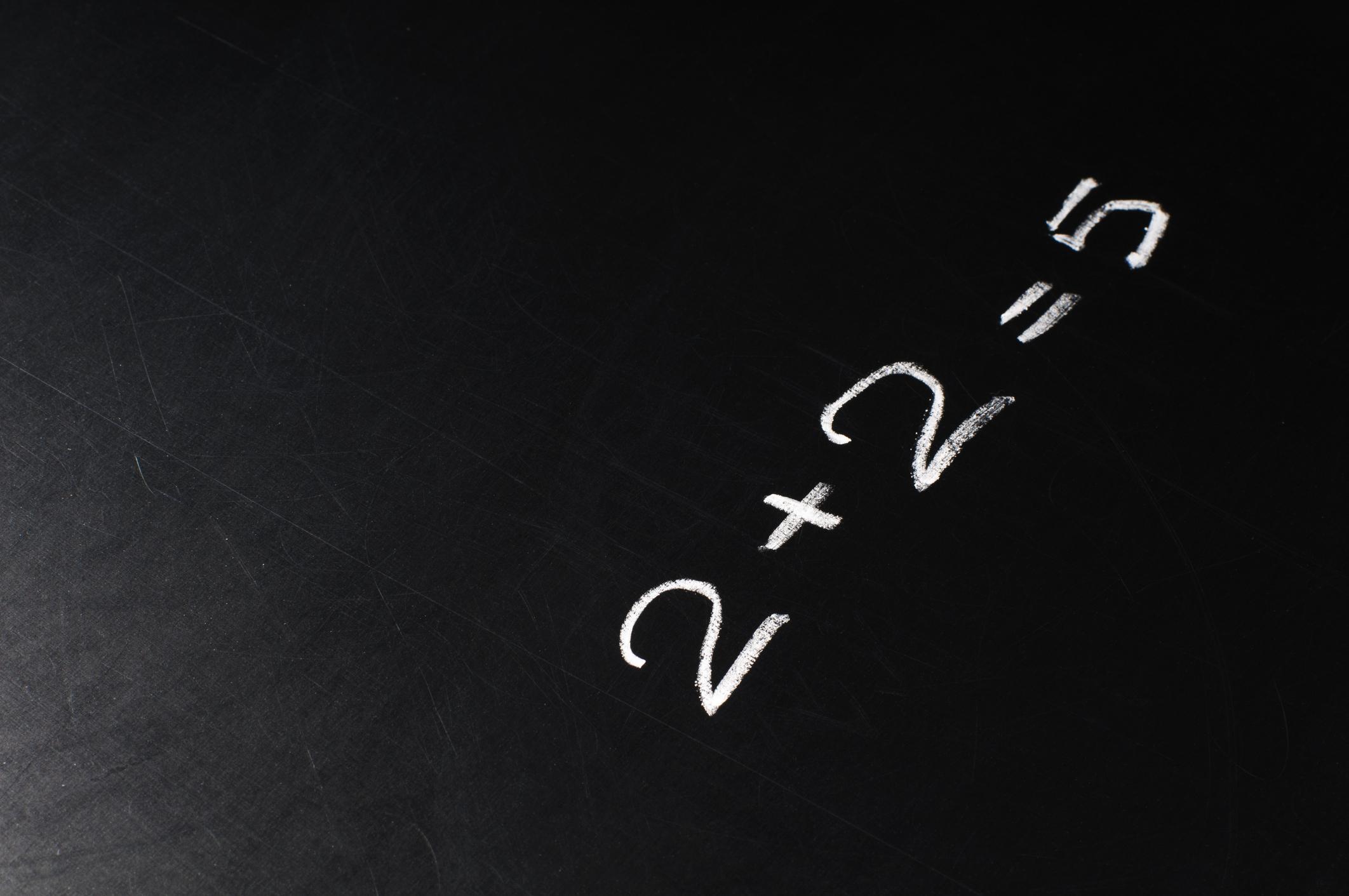 2+2=5 written on a chalkboard.