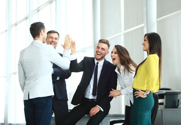 Group of professionally dressed adults smiling and high-fiving