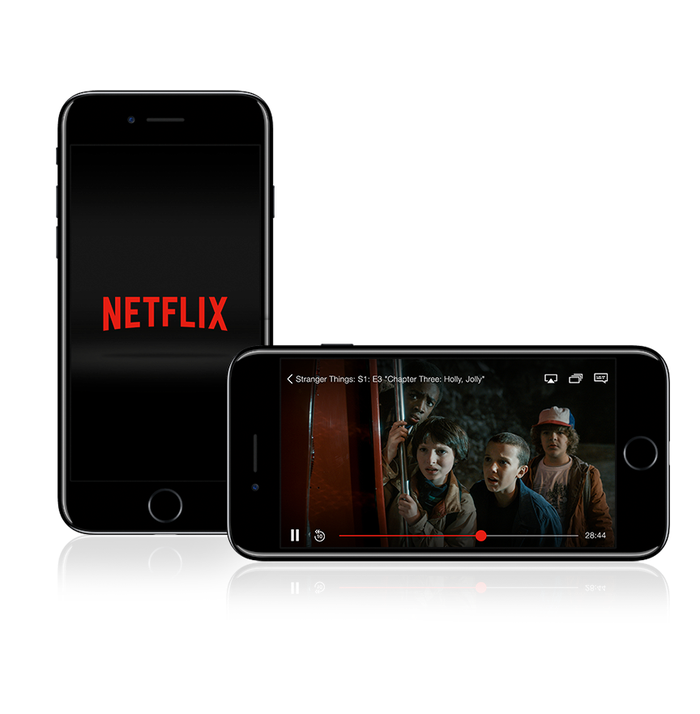 One iPhone standing vertically showing the Netflix logo, and another laying landscape showing a scene from the Netflix original series Stranger Things