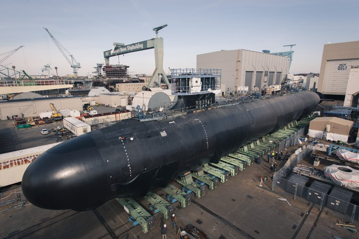 The USS Delaware in dry dock at a shipyard during the day.