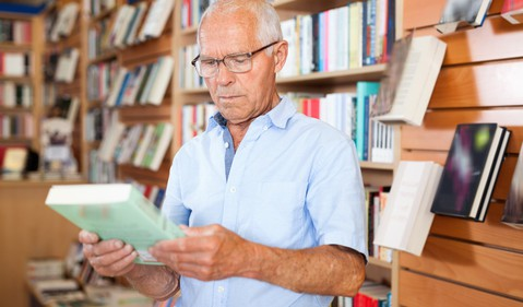 senior man looking at book in bookstore_GettyImages-1001426690