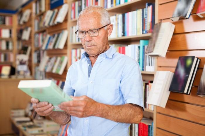 Senior man holding book in bookstore.