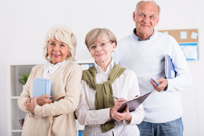 Three seniors holding notebooks and clipboards while standing together