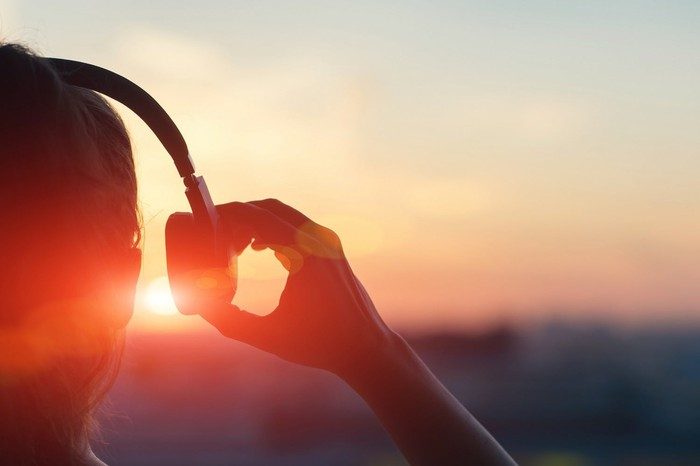 Woman with headphones watching sunset.