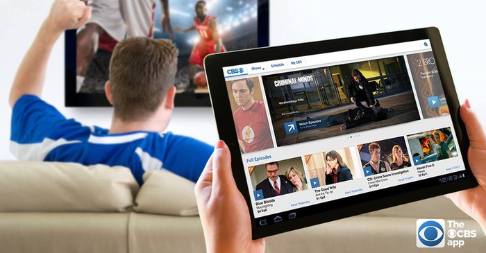 A tablet displaying the CBS All Access app and a man on a couch watching sports in the background