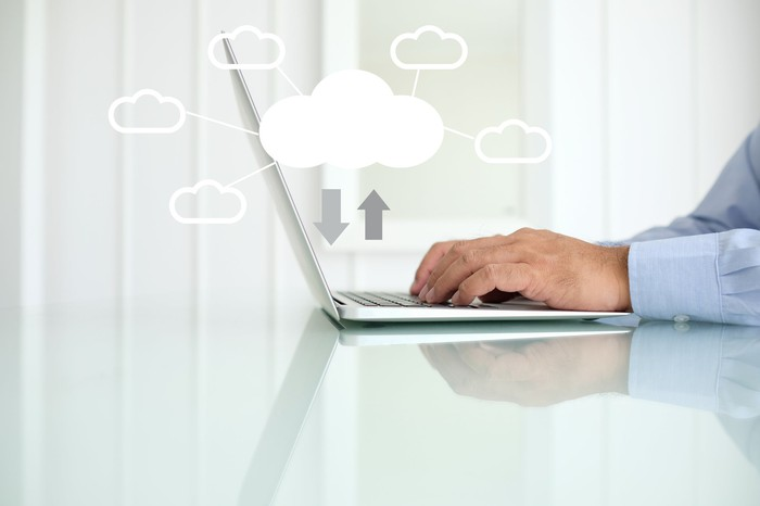 A man's hands typing on a laptop keyboard with white clouds hovering above the computer