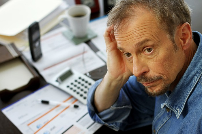 A visibly worried mature man with his hand on his head and a desk full of bills in front of him.