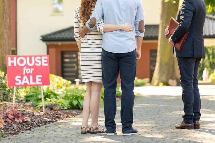A man and a woman standing next to a real estate agent and a house-for-sale sign
