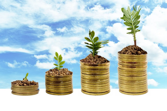 Plants growing out of progressively higher stacks of gold coins.