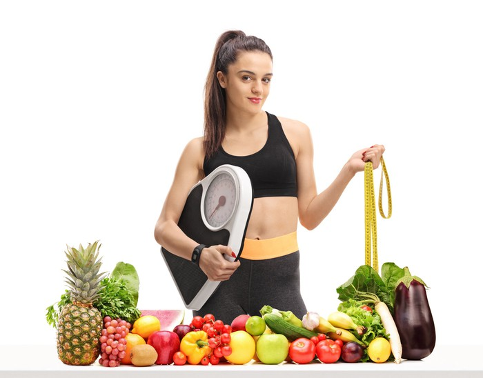 Woman holding scale and tape measure in front of a spread of fruit and vegetables
