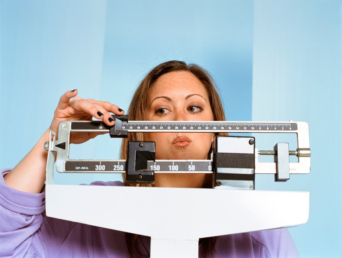 Woman checking her weight on scale.