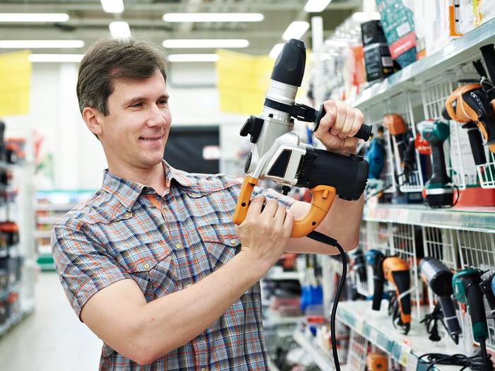 A shopper tries out a power drill.