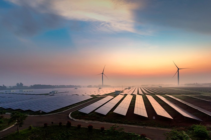 A field of solar panels with wind turbines in the background at dawn.