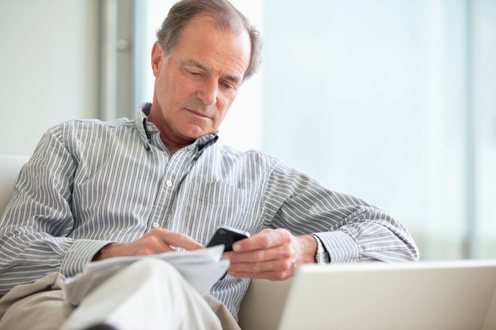 A middle-aged man sits on a sofa, looking at a phone, with a collection of papers on his knee.