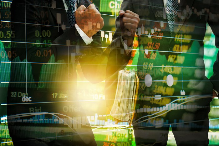 Stock index superimposed over two people in suits celebrating.