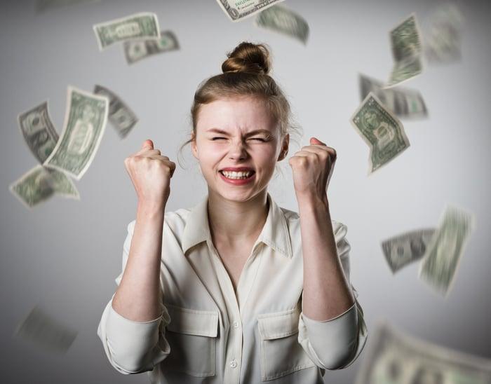 Money raining on smiling woman