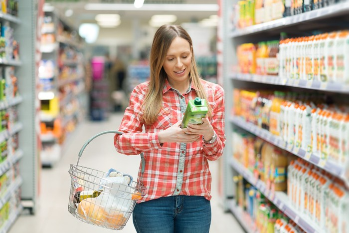 A woman studying a consumer goods product in her hands while walking down a grocery store aisle.