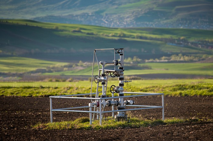 A natural gas wellhead in the middle of a field