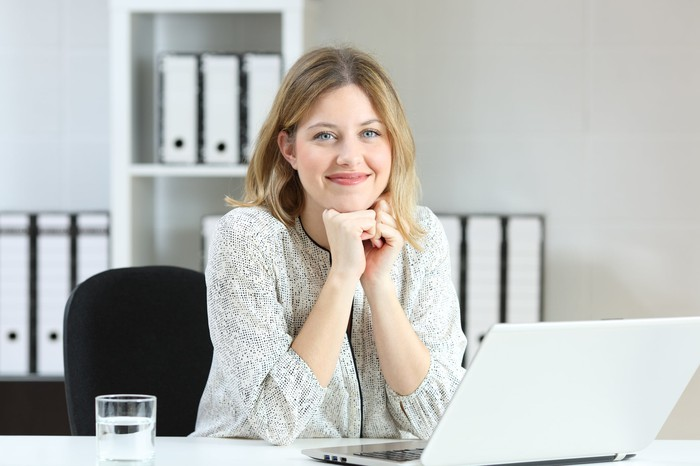 Smiling young woman at laptop.