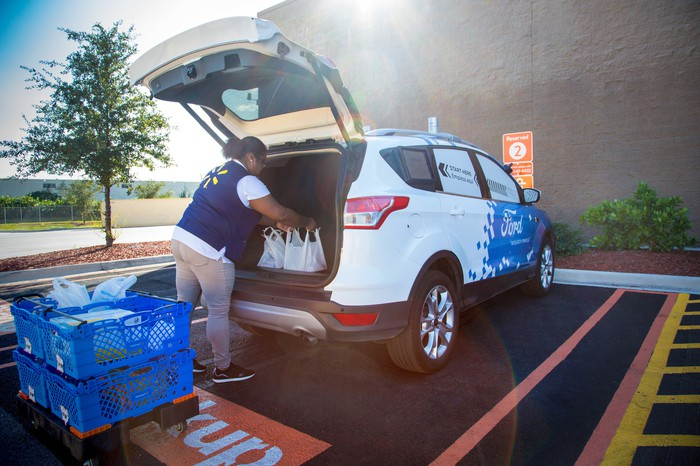 A Walmart employee loading grocery bags into the back of a Ford car.