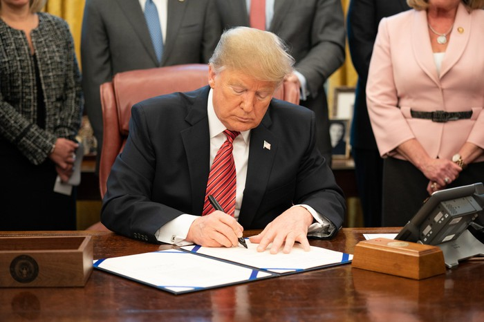 President Trump signing a bill at his desk in the Oval Office.