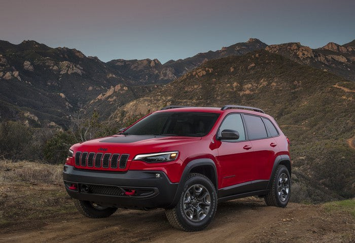 A red and black 2019 Jeep Cherokee parked up in the mountains.