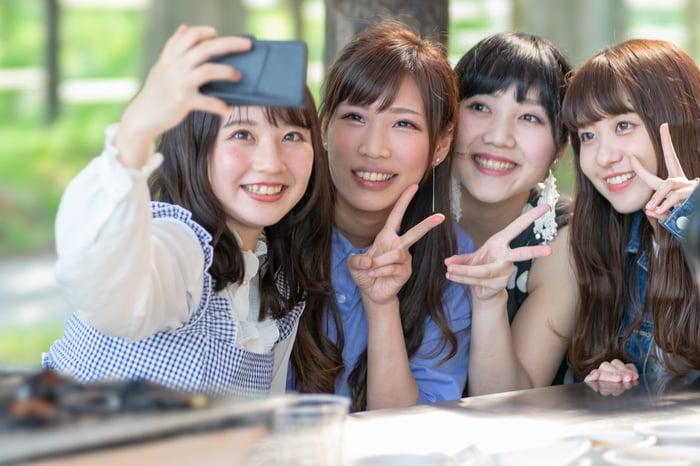 Four Japanese women take a selfie.