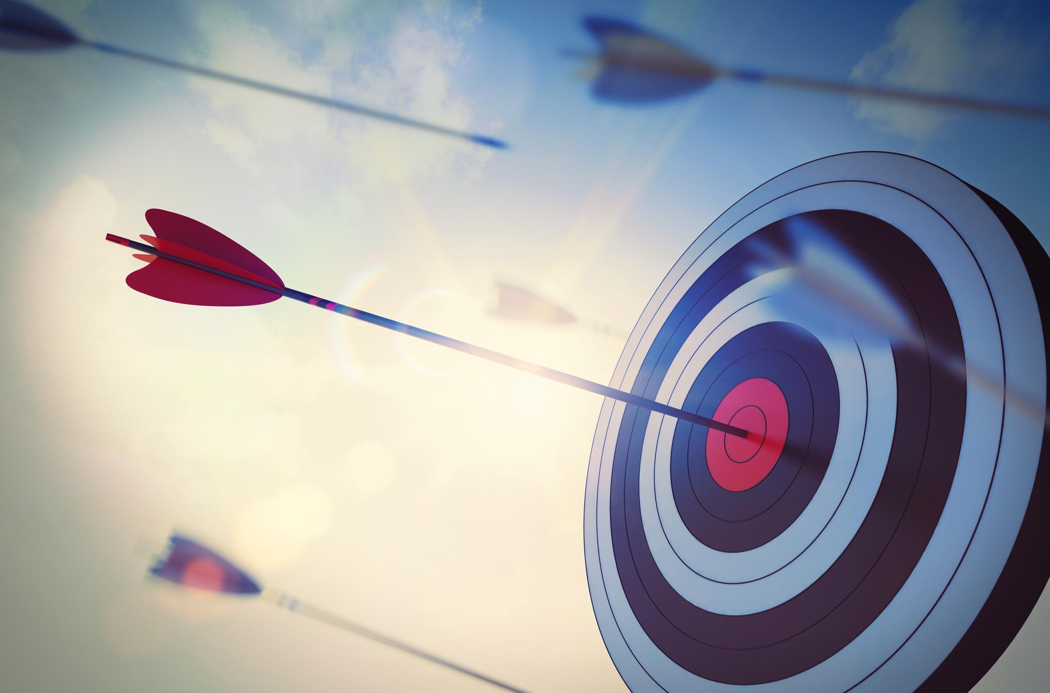 An arrow in the bulls eye of a target.