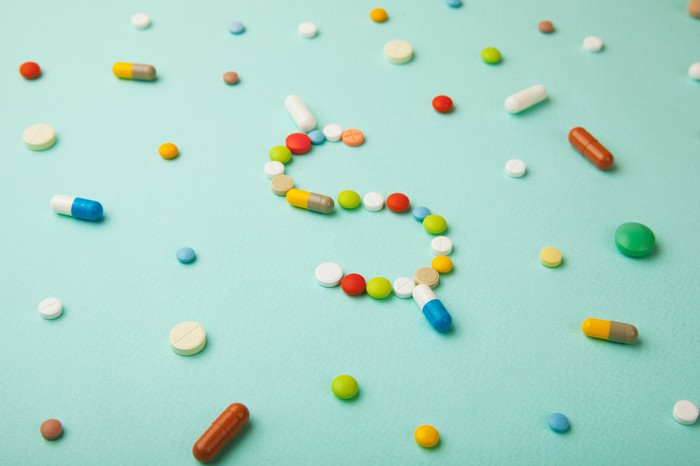 Pills of different colors scatter on a surface with some in the center arranged to form a dollar sign