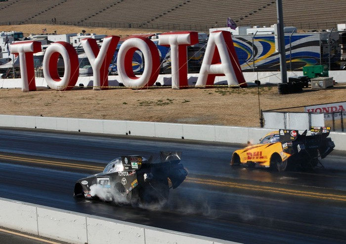 Two drag cars racing in front of the Toyota logo.