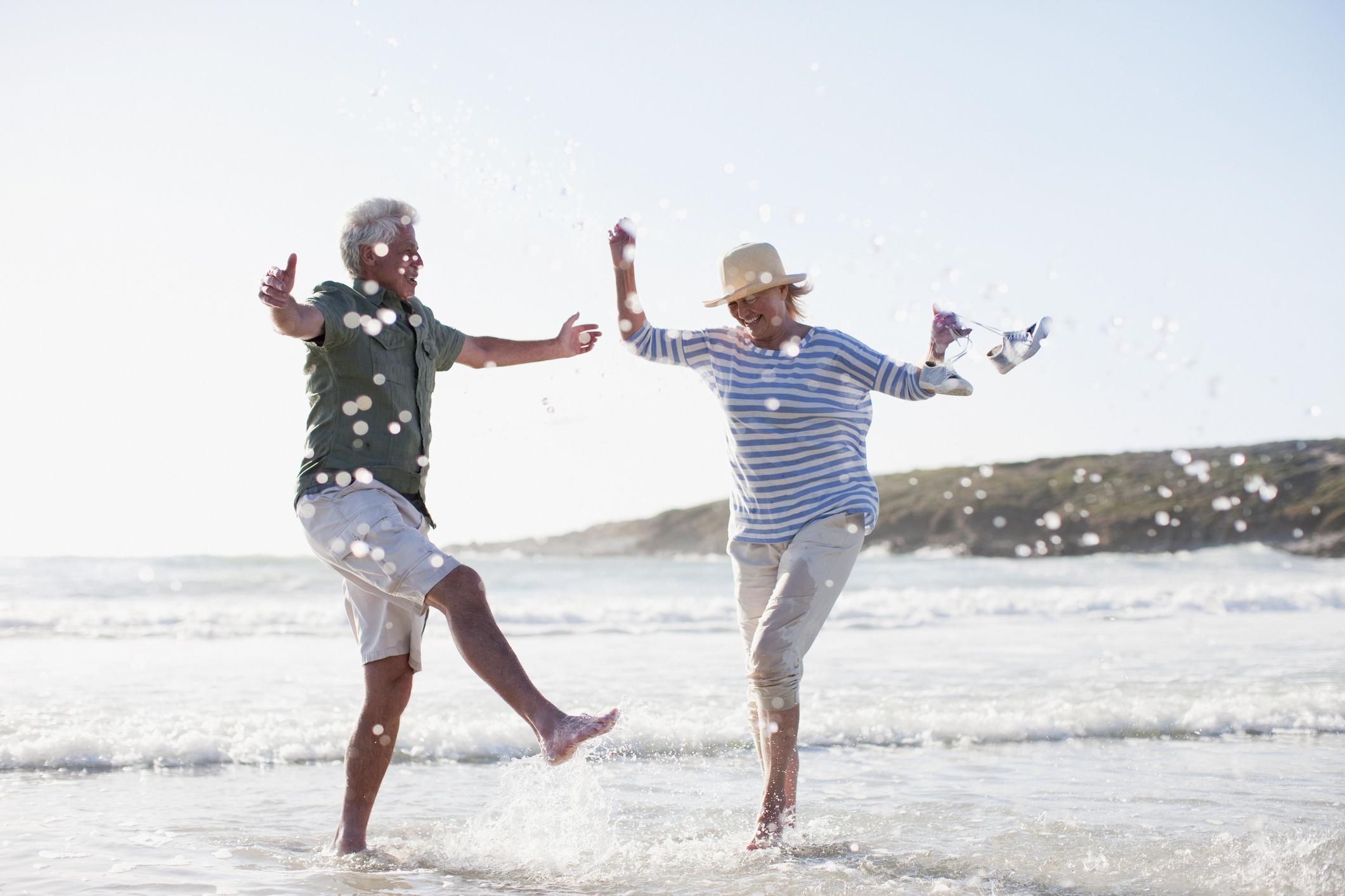 Two older folks splashing in the ocean