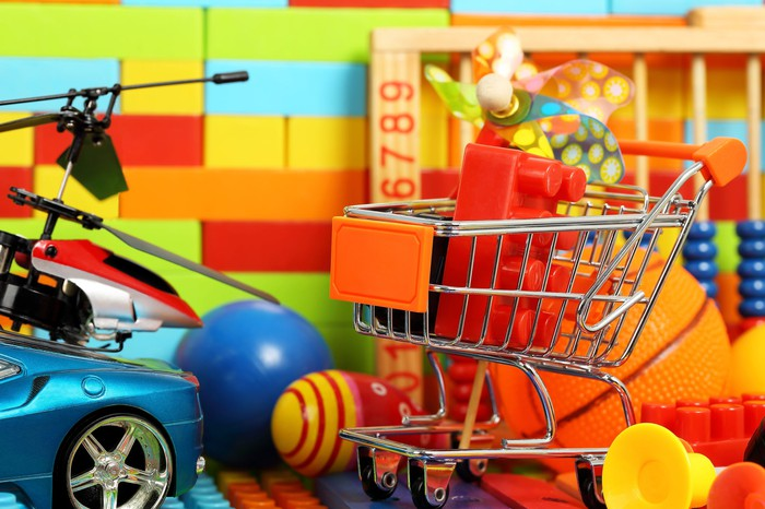 Toy shopping car with a building block in it next to other toy figurines