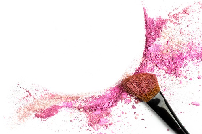 A cosmetic brush with a sweep of rose-pink powder