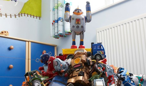 triumphant robot toy on pile of toys
