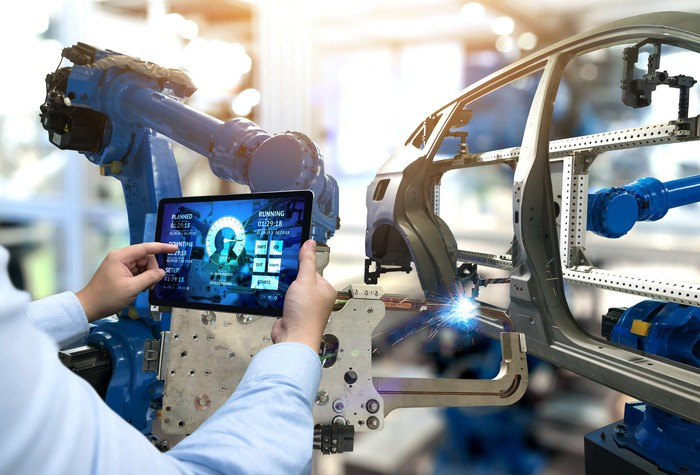 An automotive engineer uses a tablet to monitor an assembly line.