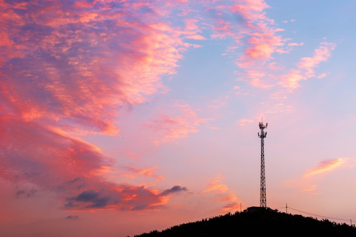 A cellular tower on a hill with pink clouds.
