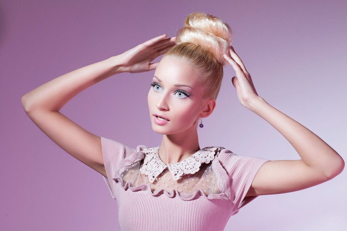 A model imitating a Barbie doll wearing a pink dress.