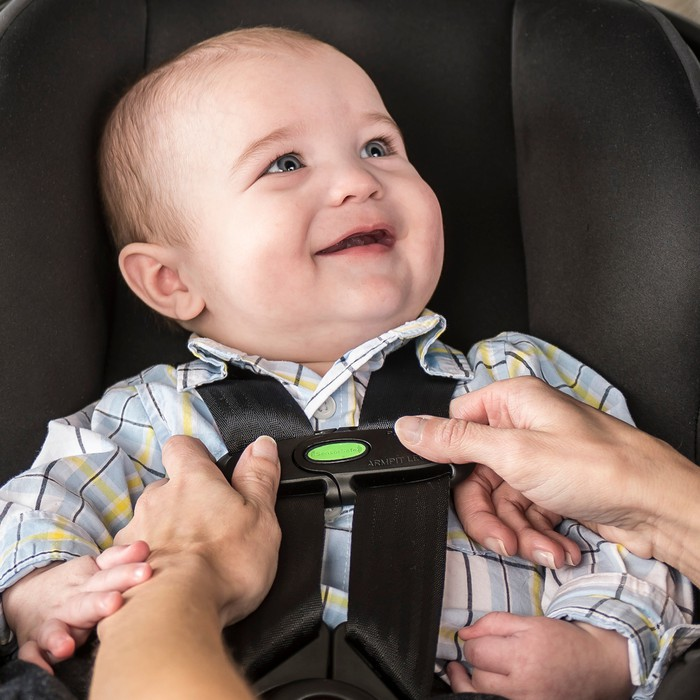 A baby is snapped into a car seat.