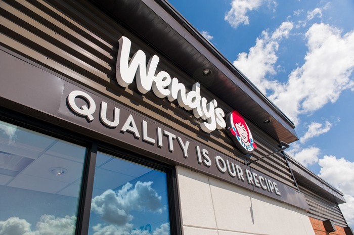 An exterior shot of a renovated Wendy's restaurant with a background of clouds and blue sky.