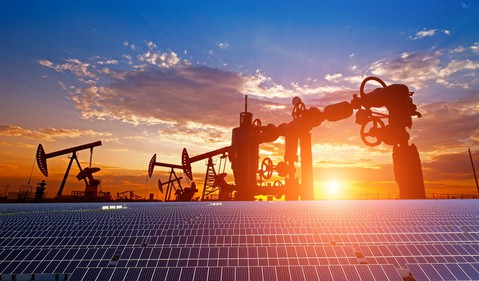 Oil pumps, a natural gas well, and solar panels with the sun setting in the background.