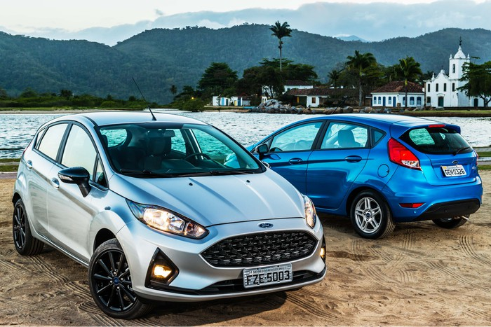 Two Ford Fiestas, subcompact hatchbacks, are shown parked on a lakefront.